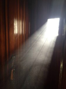 Photo shows light streaming in to a dark room through a window. Dust particles can be seen, thick, in the light.