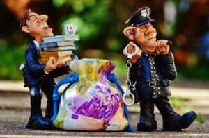 Two claymation characters, one is a policeman with handcuffs and one is a man in a suit carrying a stack of books. There is a bag of printed money between them.