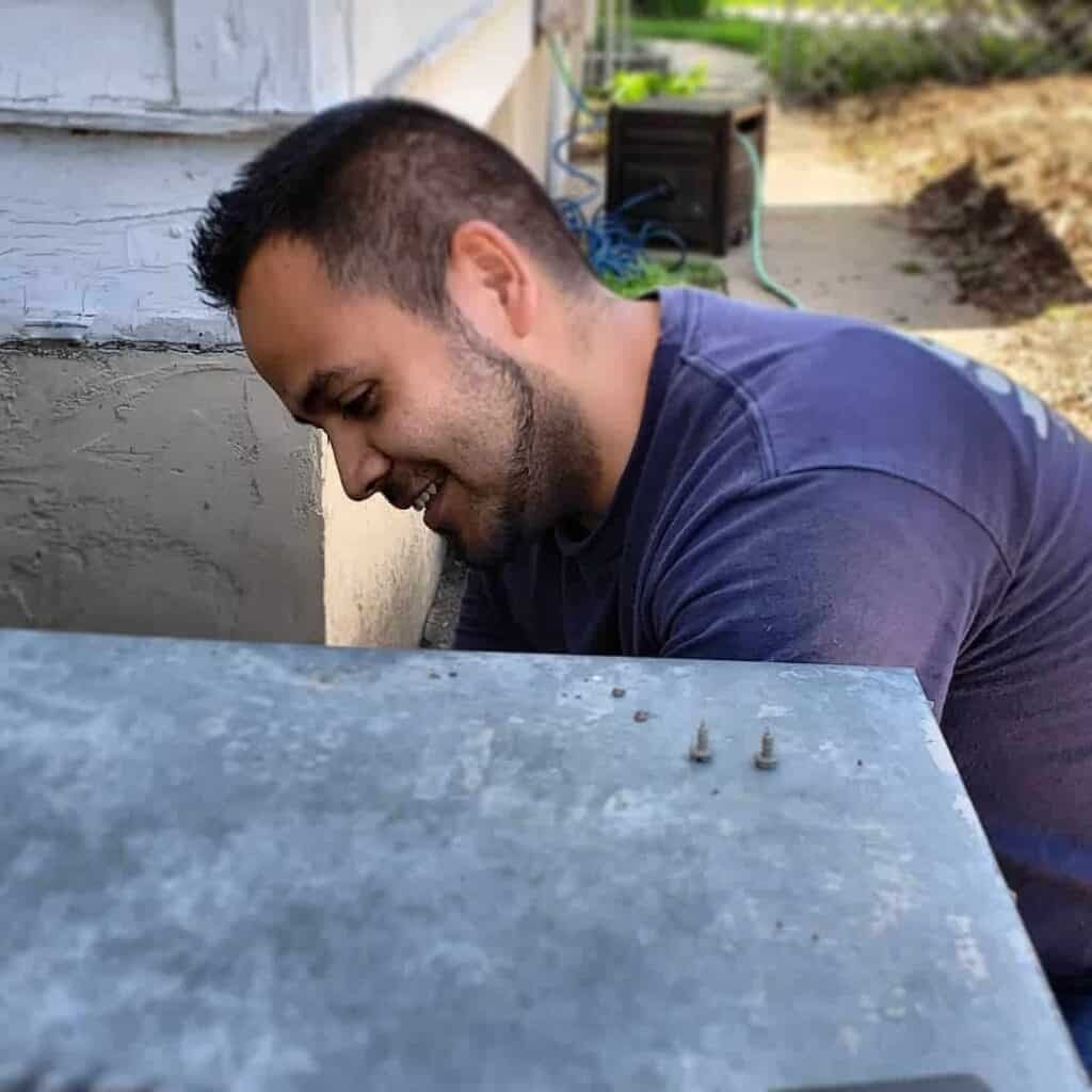 HVAC technician, Jose, is pictured addressing an air conditioning problem during a routine spring hvac maintenance