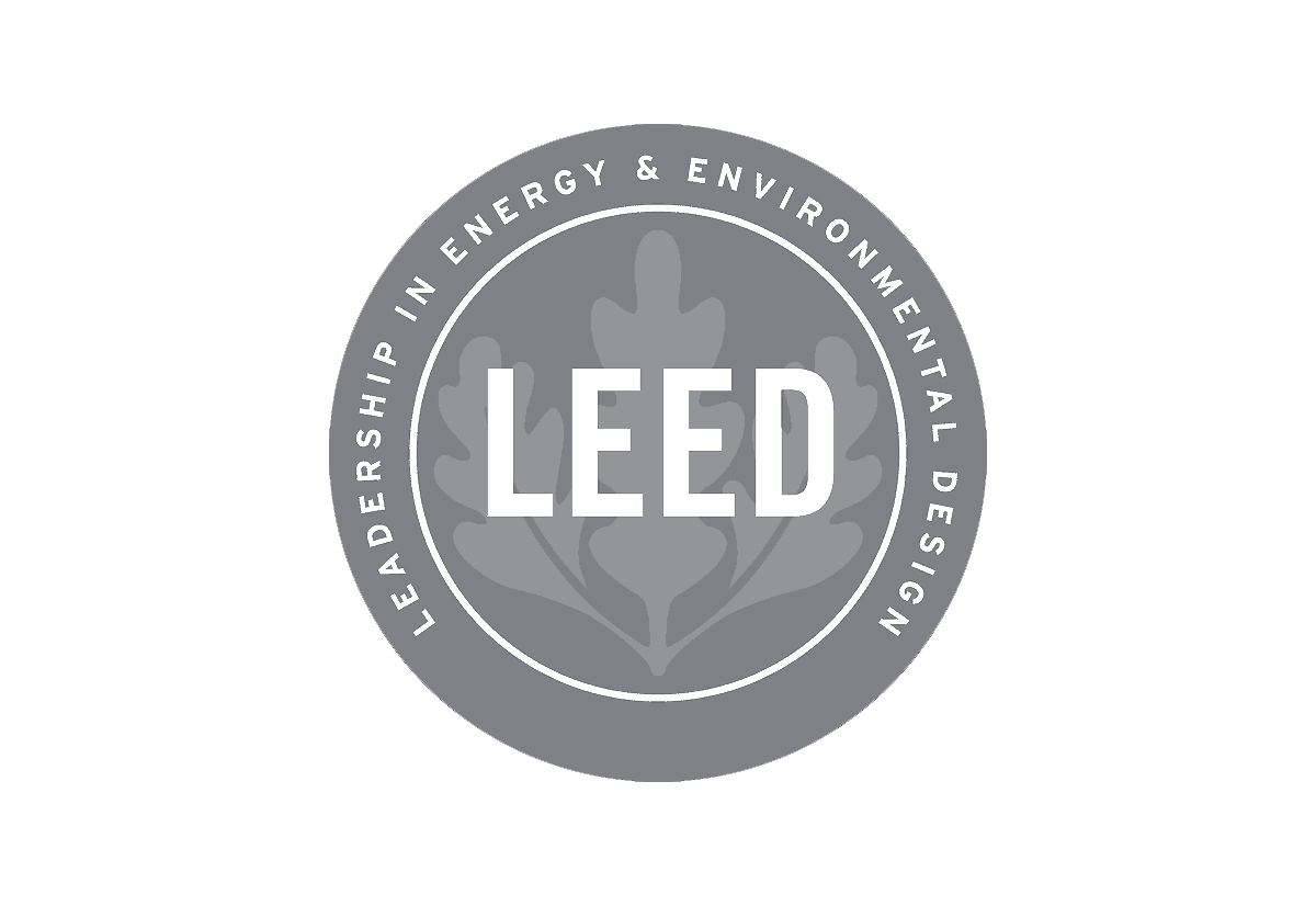"This logo is a silver disc with a leaf shaped overlay and the lettering LEED ""Leadership in Energy & Environmental Design"" printed around the edge of the circle"