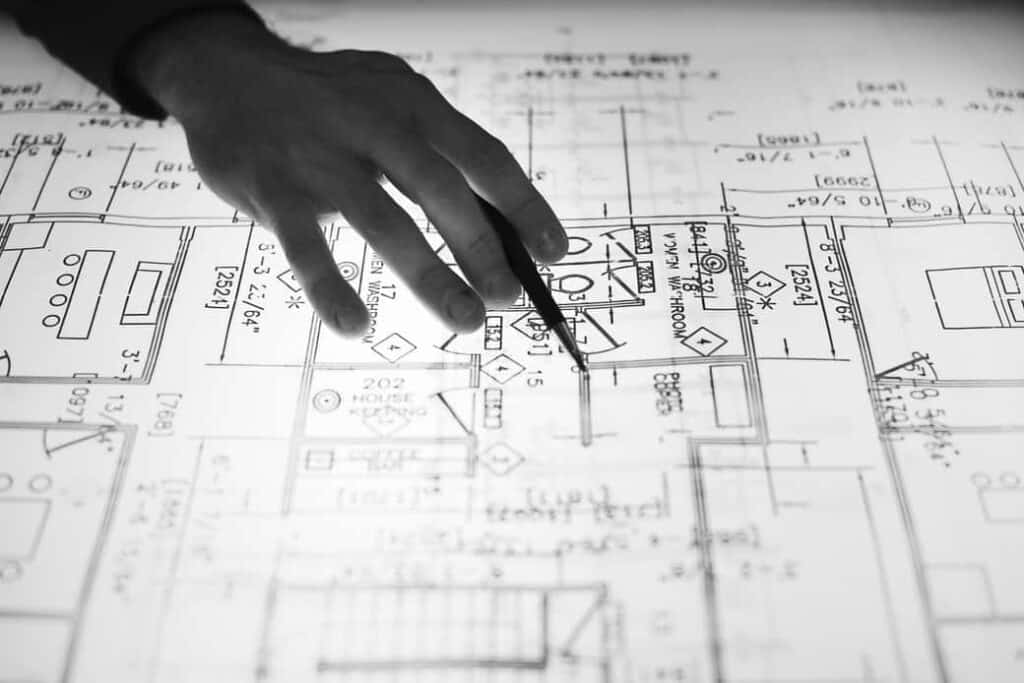 Photo of a hand over computer aided drafting plans pointing out parts of the duct design