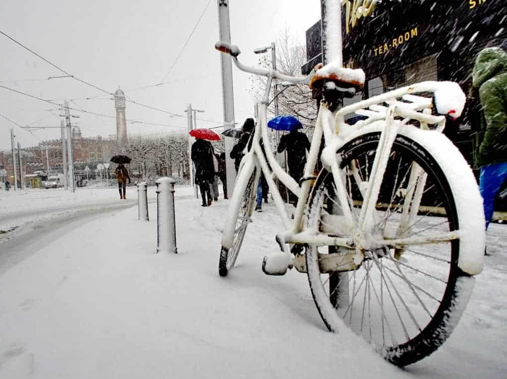 Photo of a bicycle parked next to a sidewalk. The sky is gray and the sidewalk, street and bike are covered in snow.