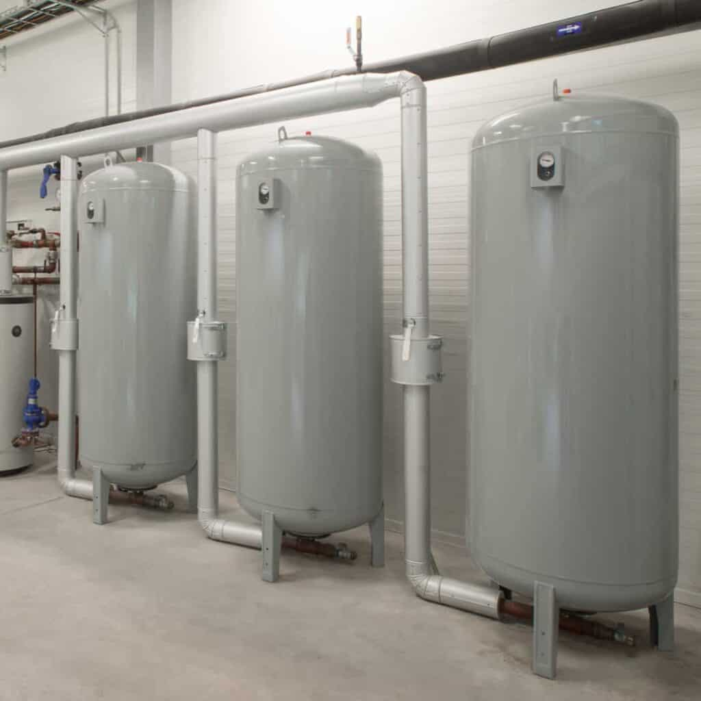 Photo of a boiler room with 3 large tanks lined up in a row. Each has a gauge mounted on it. The tank on the right has a pipe coming off of it and feeding into a pipe that comes off the next, and so on, down the line. There is an individual shut-off valve mounted on the pipes where they come off of each tank.