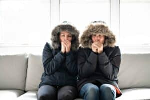 Photo of a man and woman sitting on a sofa. They are wearing hooded parkas and warming their hands with their breath.