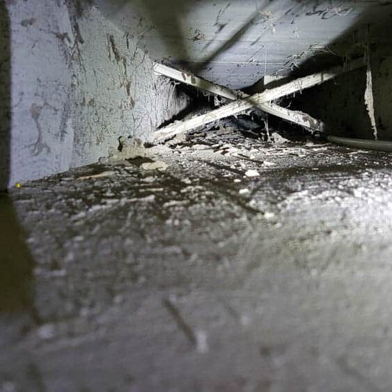 Photo looking into a return air duct before cleaning shows thick dust and debris built up.
