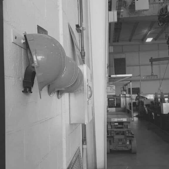 Black and white photo of hard hats hanging on a wall in the sheet metal shop.