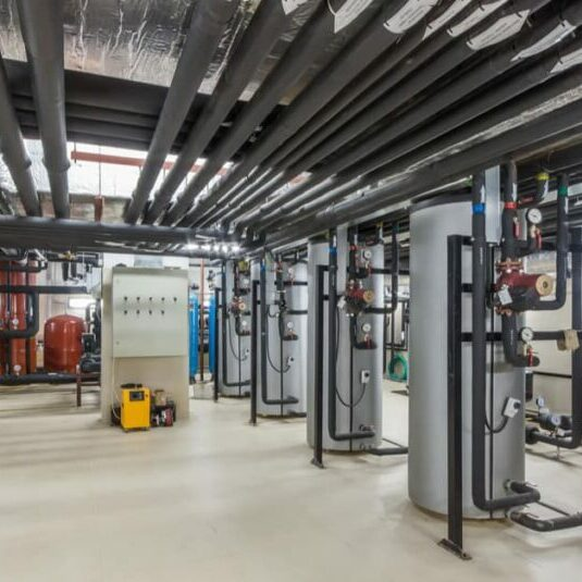 Looking into a boiler room, with several 8 foot tall, large, modern water tanks line up on the right side of the room. Overhead, rows of insulated piping. In the middle of the room is a modern controls and monitoring system.