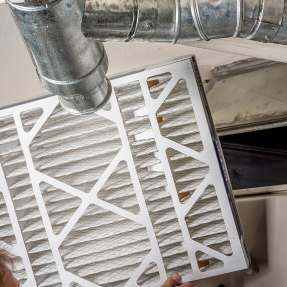 A person is inserting a new furnace filter. The ducting leading to the furnace is visible.