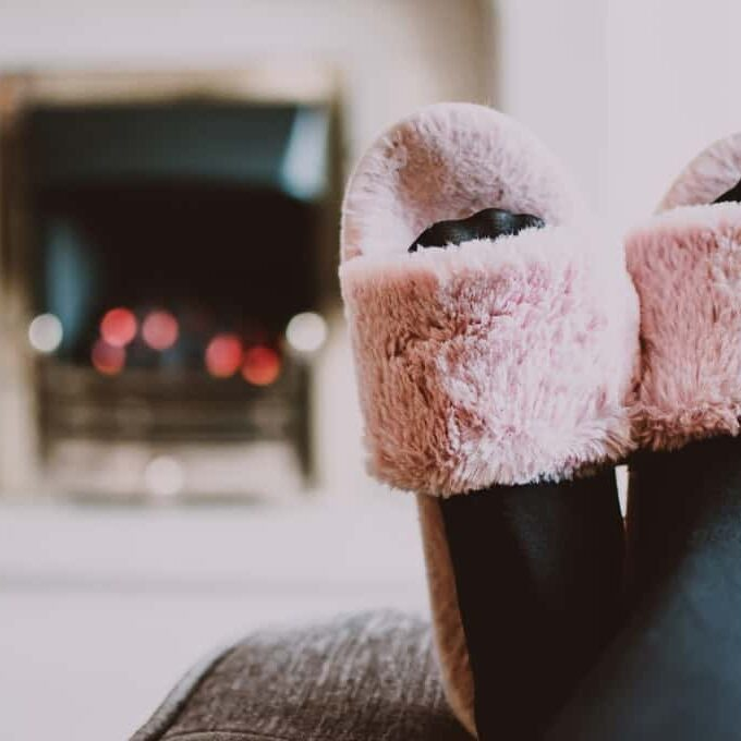 Photo of slippered feet on a footstool, in the background, a fire roars in a fireplace