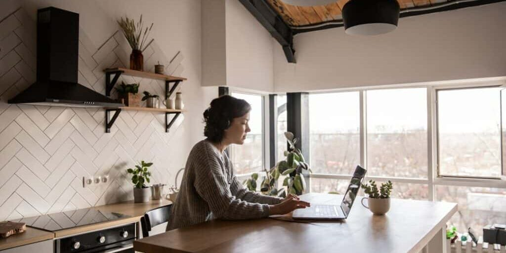 Photo of a young woman standing in a modern kitchen using her laptop on the counter, researching reasons why her air conditioner is turning on and off.