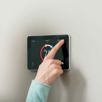 Photo of woman adjusting iComfort Smart Thermostat